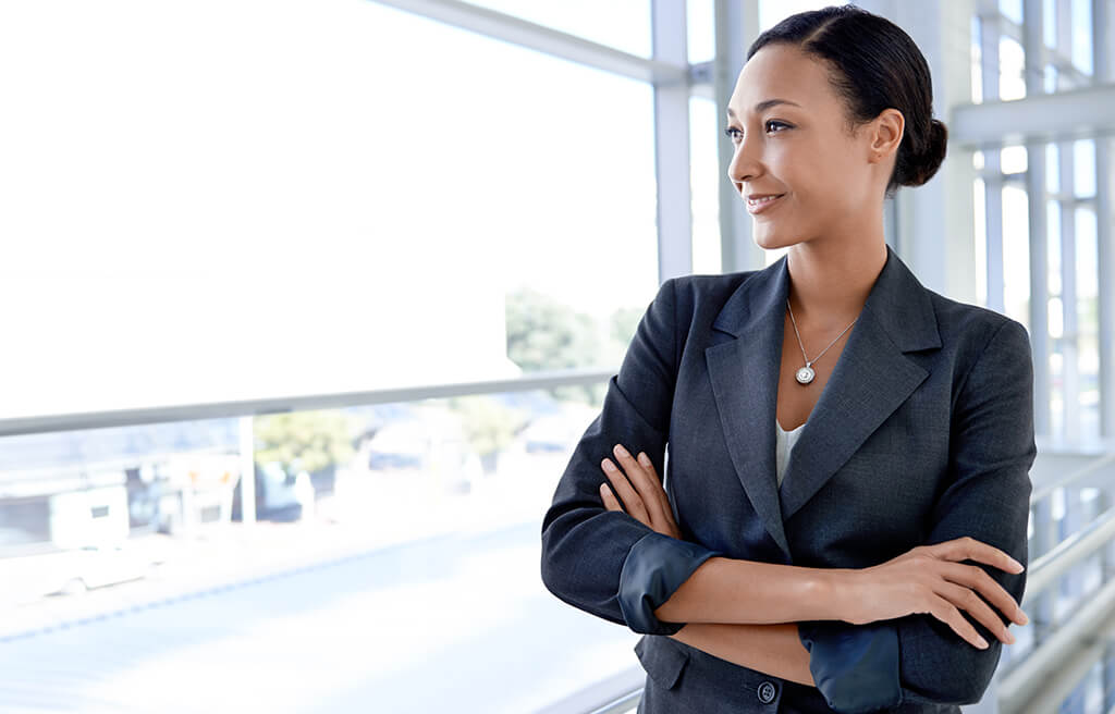smiling business woman looking out office window