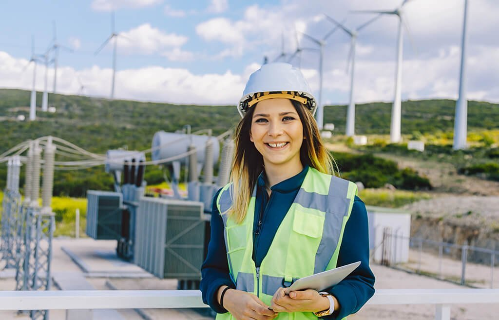 female energy expert in front of wind power station